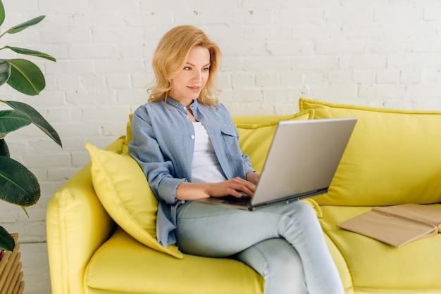 Junge dame, die ein buch auf gemütlicher gelber couch liest