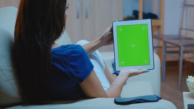 Junge dame, die ein tablet mit grünem bildschirm auf der couch hält. frau liest, mit blick auf die vorlage chroma-key isolierte smart-notebook-anzeige mit technologie-internet auf einem bequemen sofa liegend.