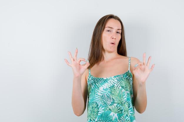 Junge dame, die eine gute geste in der bluse zeigt und glücklich aussieht, vorderansicht.