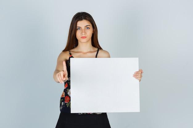 Junge dame, die eine leere leinwand hält, eine winzige geste in bluse, rock zeigt und ernste vorderansicht sieht.