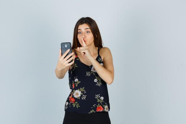 Junge dame, die eine stille-geste zeigt, während sie einen videoanruf in der bluse tätigt und vorsichtig aussieht, vorderansicht.