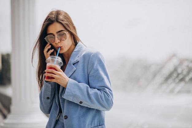 Junge dame, die eistee im park trinkt und am telefon spricht