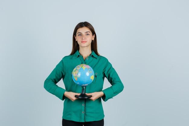 Junge dame, die erdkugel im grünen hemd hält und zuversichtlich schaut. vorderansicht.