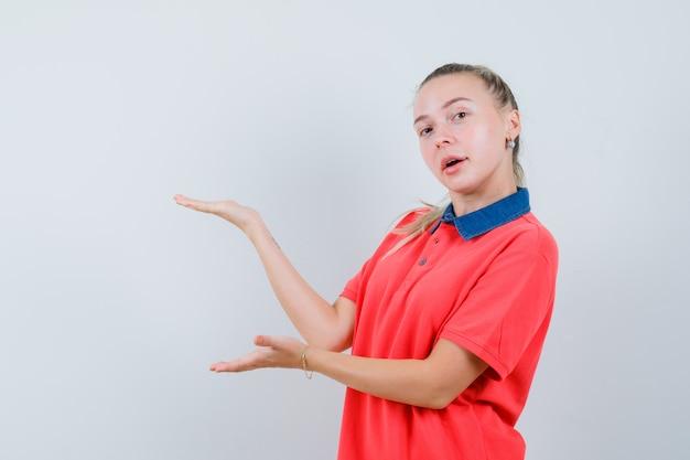 Junge dame, die etwas im t-shirt begrüßt oder zeigt und selbstbewusst aussieht