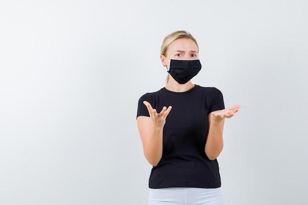 Junge dame, die etwas in t-shirt, hose, medizinischer maske hält und zögerlich aussieht