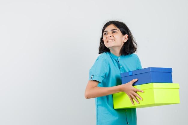 Junge dame, die farbige geschenkboxen im blauen hemd hält und froh schaut.
