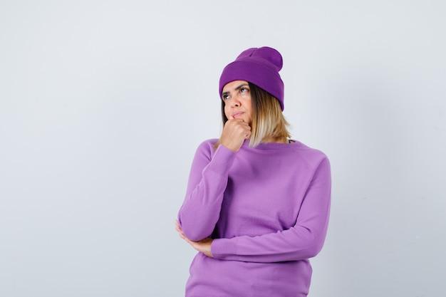 Junge dame, die faust am kinn in lila pullover, mütze hält und nachdenklich aussieht. vorderansicht.