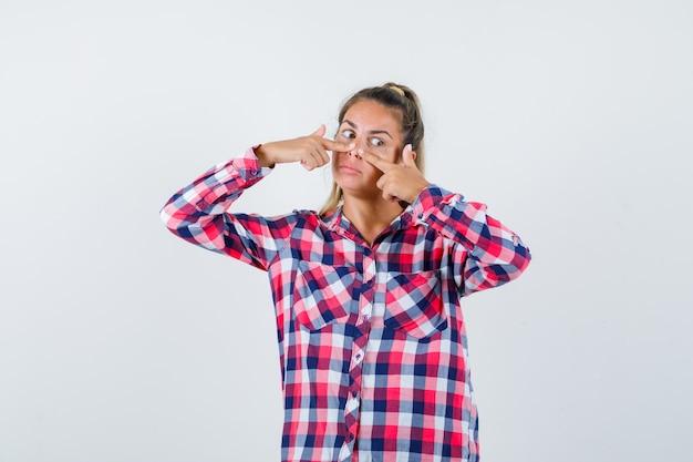 Junge dame, die finger auf nase im karierten hemd hält und nachdenklich aussieht. vorderansicht.