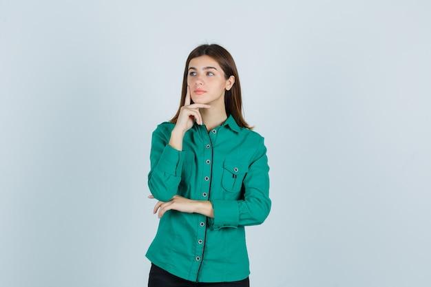 Junge dame, die finger setzt, um auf kinn im grünen hemd zu stützen und nachdenklich, vorderansicht zu schauen.