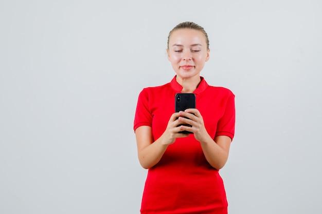 Junge dame, die foto auf handy in rotem t-shirt nimmt und fröhlich schaut