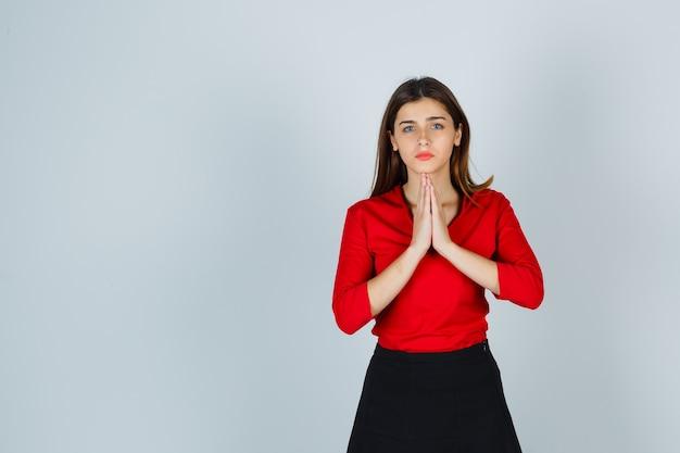 Junge dame, die gefaltete hände in der flehenden geste in der roten bluse zeigt