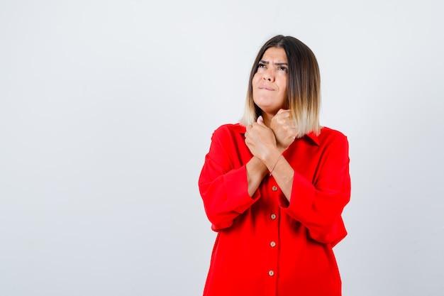 Junge dame, die gekreuzte fäuste unter dem kinn im roten übergroßen hemd hält und nachdenkliche vorderansicht schaut.