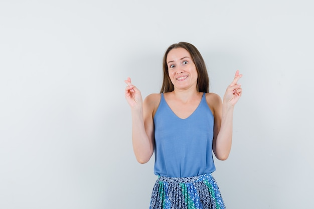 Junge dame, die gekreuzte finger in bluse, rock zeigt und fröhlich sieht, vorderansicht.