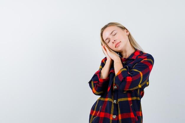 Junge dame, die gesicht auf ihren händen im karierten hemd kissen und schläfrig aussieht. vorderansicht.