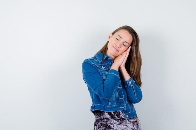 Junge dame, die gesicht auf ihren händen in bluse, jeansjacke polstert und schläfrig aussieht, vorderansicht.