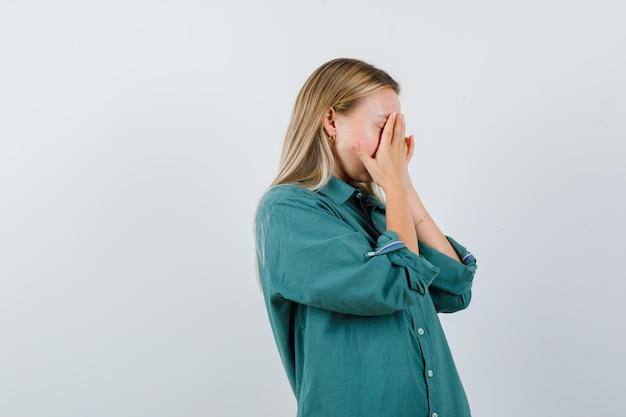 Junge dame, die gesicht mit den händen im grünen hemd bedeckt und beschämt schaut.