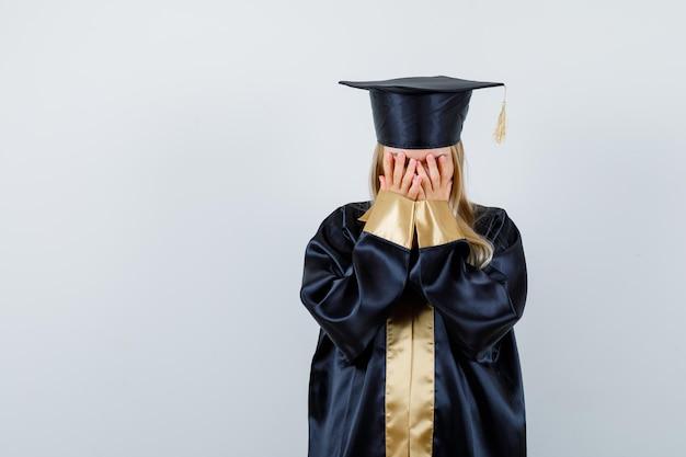 Junge dame, die gesicht mit den händen in akademischer kleidung bedeckt und verängstigt aussieht.
