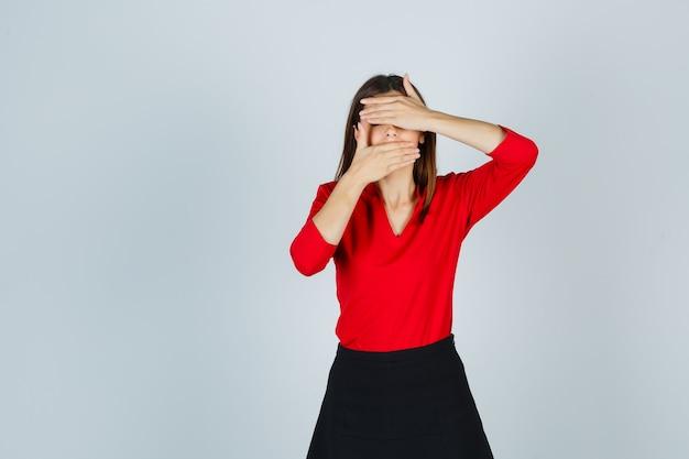Junge dame, die gesicht mit händen in roter bluse, schwarzem rock bedeckt und beschämt aussieht