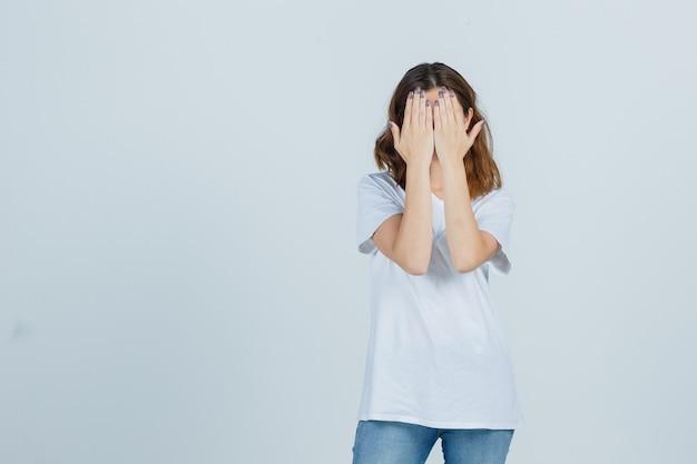 Junge dame, die gesicht mit händen in t-shirt, jeans bedeckt und ernst schaut. vorderansicht.