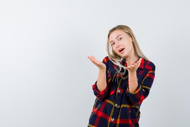Junge dame, die geste im karierten hemd zeigt und glücklich schaut. vorderansicht.