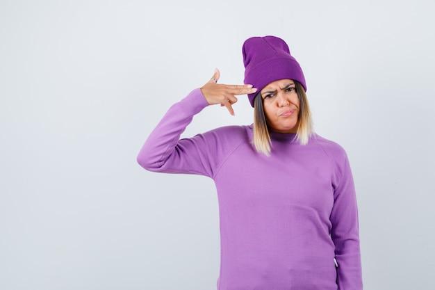 Junge dame, die gewehrgeste in lila pullover, mütze zeigt und gelangweilt aussieht. vorderansicht.
