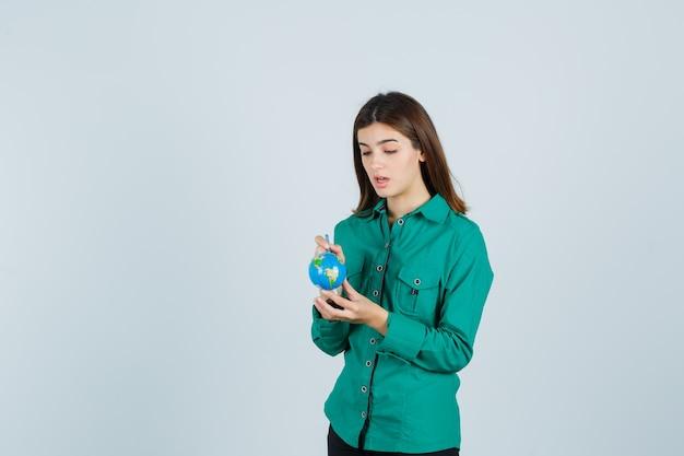 Junge dame, die globus hält und im hemd darauf zeigt und konzentriert schaut. vorderansicht.