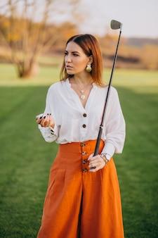 Junge dame, die golf spielt