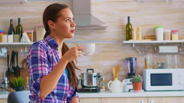 Junge dame, die grünen tee trinkt und beim frühstück am tisch in der küche lächelt. frau, die morgens ein gesundes heißes kräutergetränk mit teekanne und teetasse genießt.