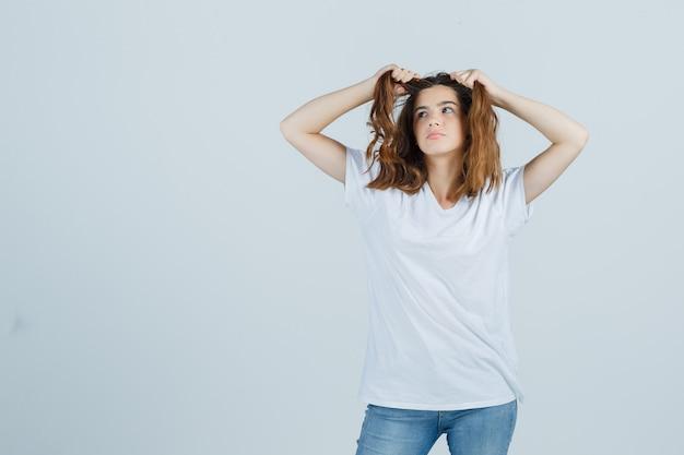 Junge dame, die haarsträhne im t-shirt, in den jeans hält und nachdenklich schaut. vorderansicht.