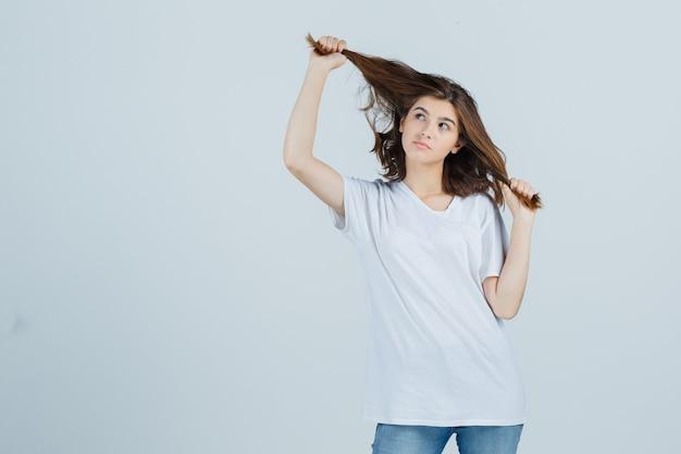 Junge dame, die haarsträhne im t-shirt, in den jeans hält und niedlich schaut. vorderansicht.