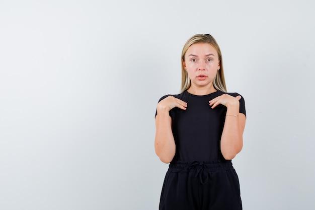 Junge dame, die hände auf brust in t-shirt, hosen hält und unentschlossen schaut, vorderansicht.