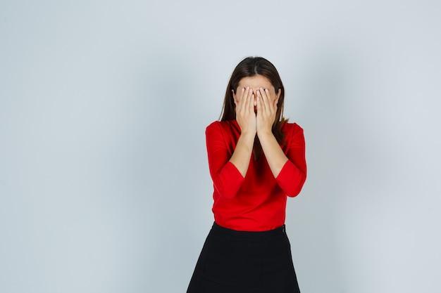 Junge dame, die hände auf gesicht in roter bluse, rock hält und erschöpft aussieht