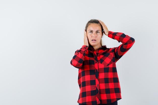 Junge dame, die hände auf kopf im karierten hemd hält und ratlos aussieht