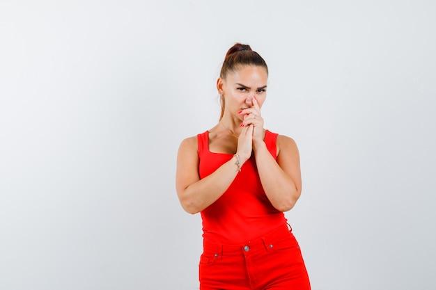 Junge dame, die hände auf mund im roten unterhemd, in der roten hose hält und nachdenklich schaut, vorderansicht.