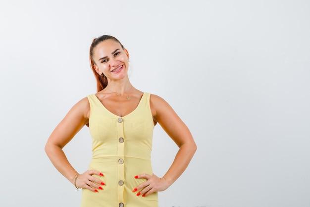 Junge dame, die hände auf taille im gelben kleid hält und fröhlich schaut. vorderansicht.