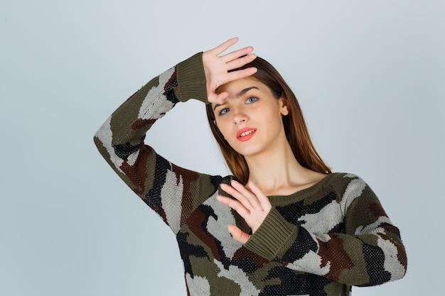 Junge dame, die hände hält, um sich in pullover, rock zu verteidigen und vernünftig auszusehen