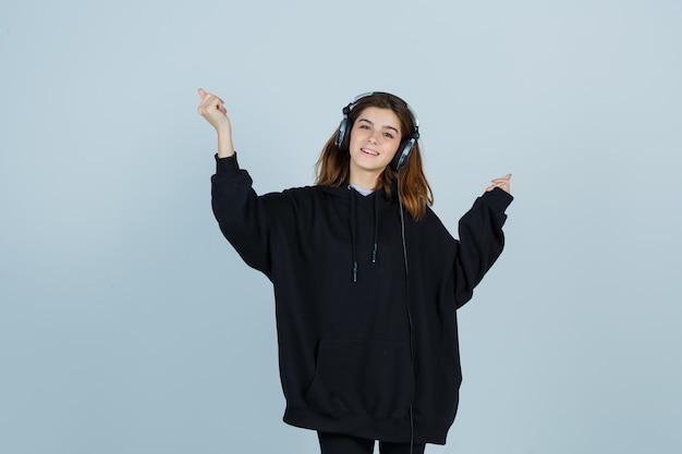 Junge dame, die hände hochhält, während musik mit handys im übergroßen kapuzenpulli, in der hose hört und energisch aussieht. vorderansicht.