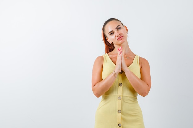 Junge dame, die hände in der gebetsgeste im gelben kleid hält und hoffnungsvoll aussieht. vorderansicht.