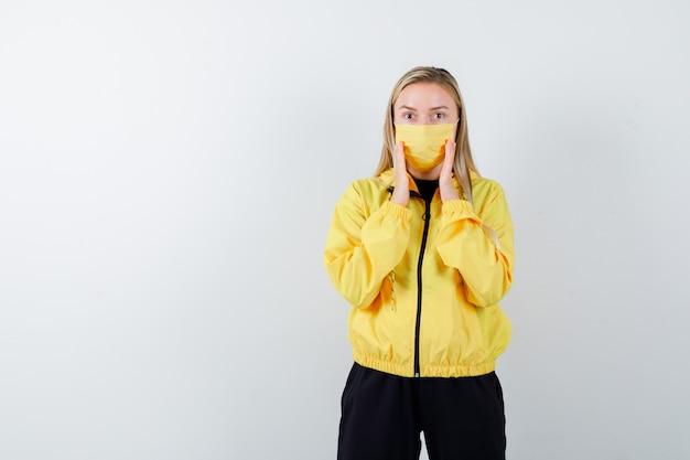 Junge dame, die hände in der nähe des mundes im trainingsanzug, in der maske hält und überrascht schaut. vorderansicht.