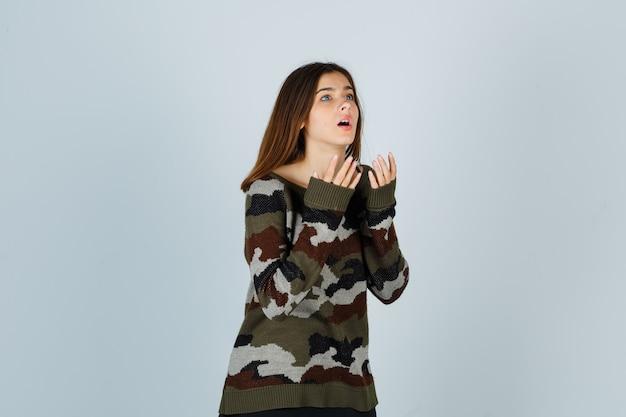 Junge dame, die hände nahe brust hält, im pullover beiseite schaut und verwirrt schaut
