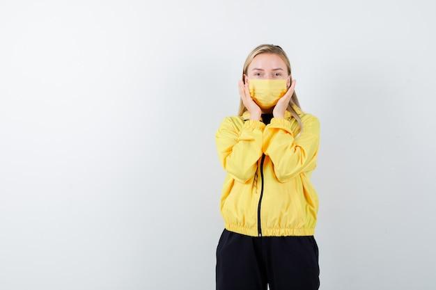 Junge dame, die hände nahe gesicht im trainingsanzug, in der maske und im aufgeregten blick, vorderansicht hält.