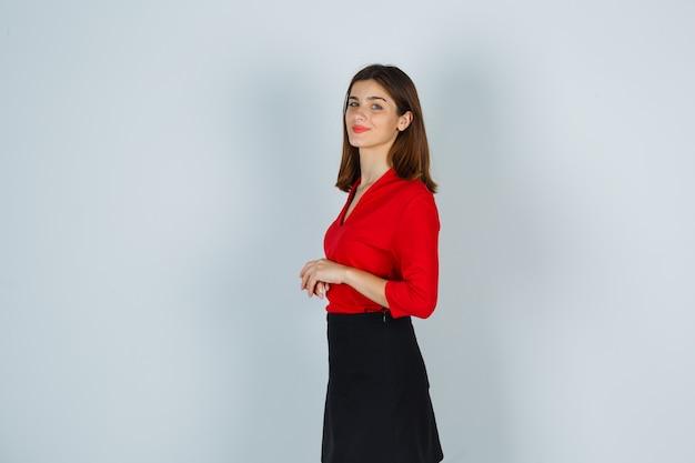 Junge dame, die hände vor ihr hält und über schulter in roter bluse schaut