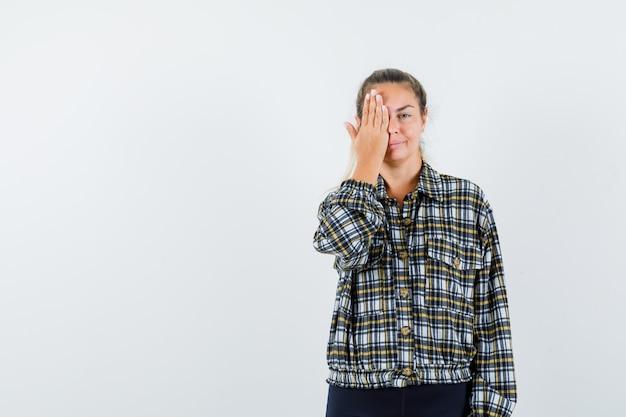 Junge dame, die hand auf auge im hemd, in den shorts hält und entzückend, vorderansicht schaut.