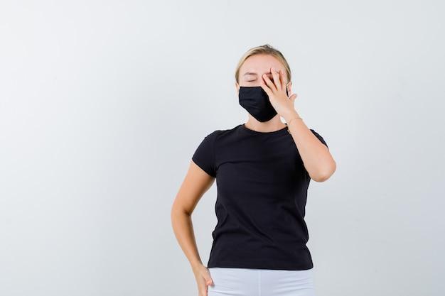 Junge dame, die hand auf auge in schwarzem t-shirt, maske und nachdenklich aussehend, vorderansicht hält.