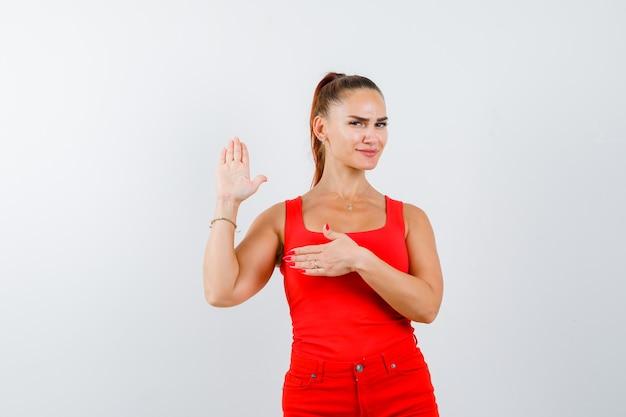 Junge dame, die hand auf brust hält, während palme im roten unterhemd, in der roten hose zeigt und selbstbewusst, vorderansicht schaut.