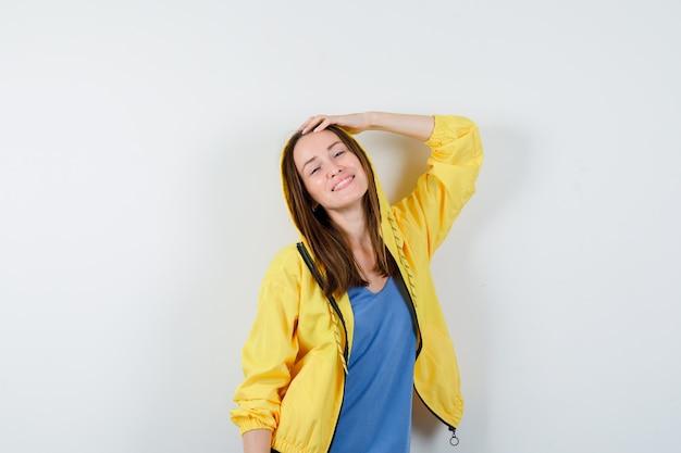 Junge dame, die hand auf dem kopf in t-shirt, jacke hält und charmant aussieht, vorderansicht.