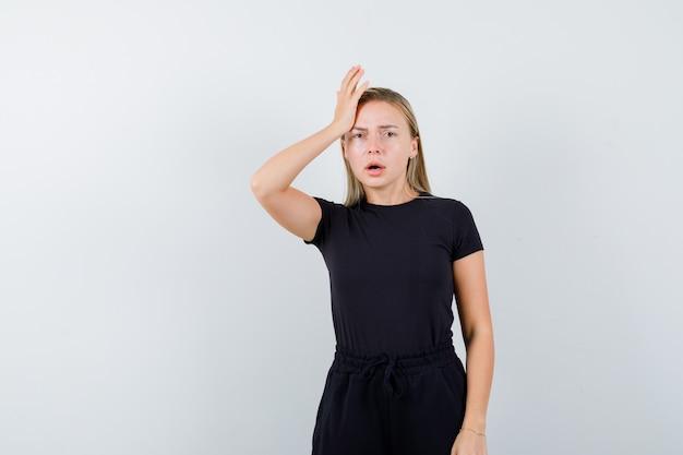 Junge dame, die hand auf kopf im t-shirt, in der hose hält und ängstlich schaut. vorderansicht.