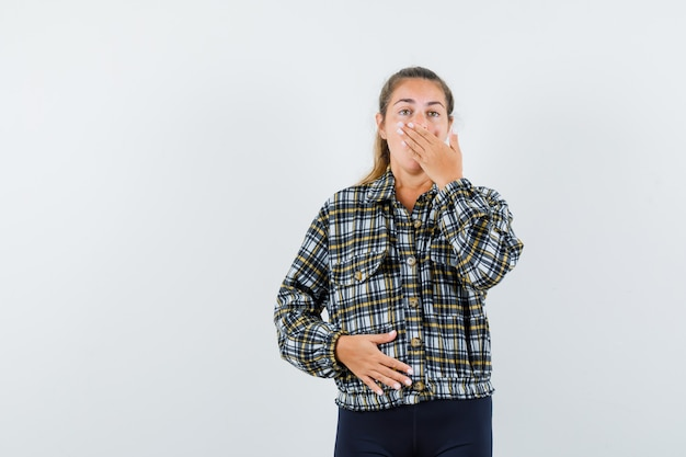 Junge dame, die hand auf mund hält, während in hemd, shorts gähnt und schläfrig aussieht. vorderansicht.