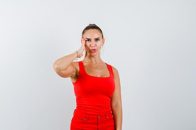 Junge dame, die hand auf schläfen im roten unterhemd, in der roten hose hält und fokussierte vorderansicht schaut.
