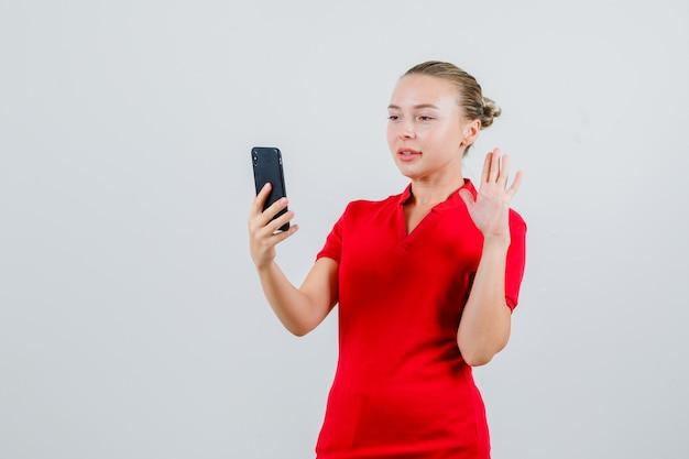 Junge dame, die hand auf videoanruf im roten t-shirt winkt